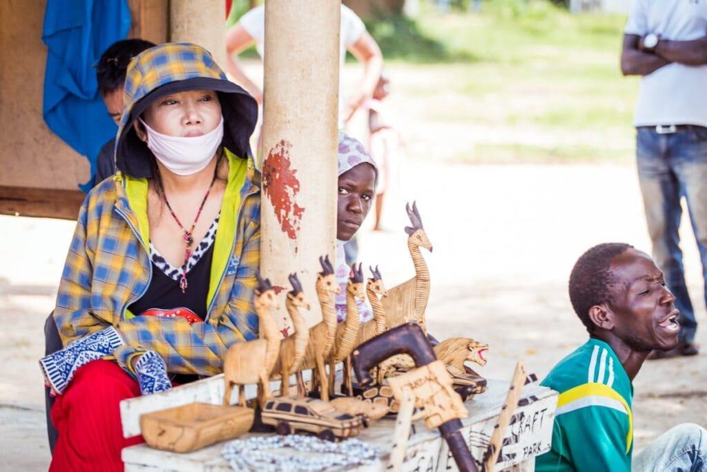 """Po """"game drive"""" na safari přijede zpět k voru-""""trajektu"""", kde už sedí další turisti a poslouchají, jak místní hrajou na nástroje a prodávají suvenýry."""