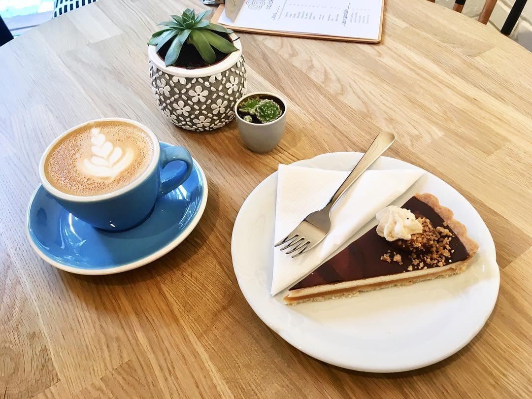 Káva a dortík na stole v Oblak Coffee