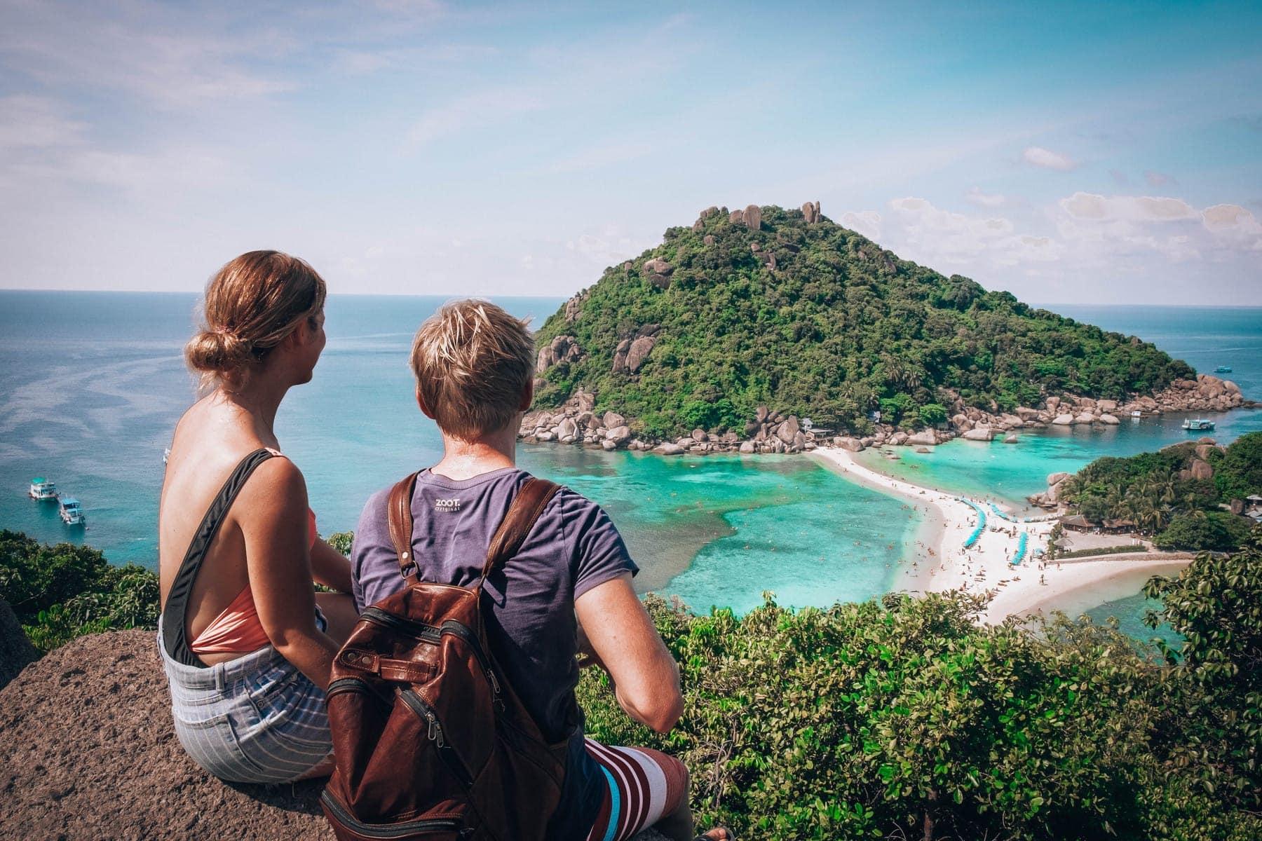 Pár sedící na kopci s výhledem na Koh Nang Yuan.